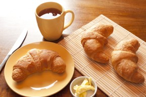 Continental breakfast with freshly baked croissants, butter and a mug of strong black filter or espresso coffee